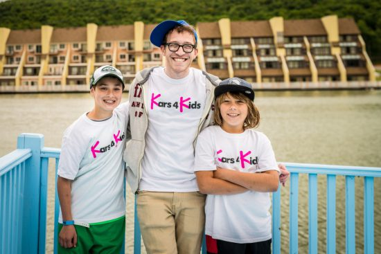 A camp instructor and 2 children wearing kars4kids t shirts